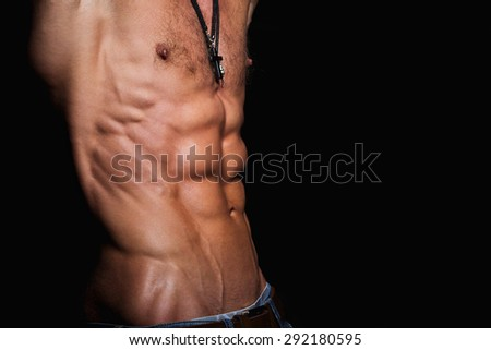 Muscular and sexy torso of young sporty man with perfect abs close up