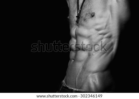 Muscular and sexy torso of young sporty man with perfect abs close up. Black and white - stock photo