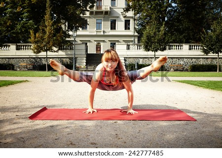 Muscular and strong yoga woman trainee exercising workout in city park - stock photo