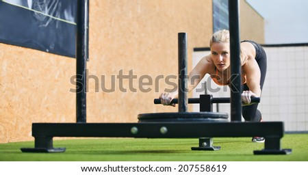Muscular and strong young female pushing the prowler exercise equipment on artificial grass turf. Fit woman exercising at crossfit gym. - stock photo