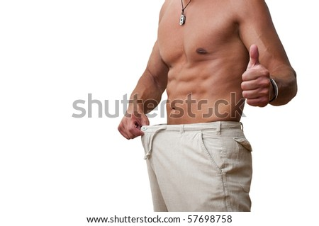 Muscular and tanned male in old pants after weight loss - stock photo