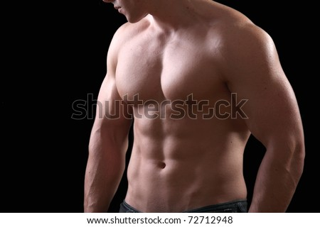 Muscular and tanned male torso isolated on black - stock photo