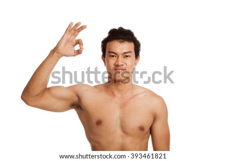 Muscular Asian man  flexing biceps show OK sign  isolated on white background