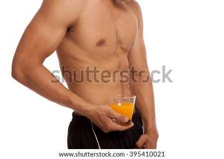 Muscular Asian man show his six pack abs with orange juice  isolated on white background - stock photo