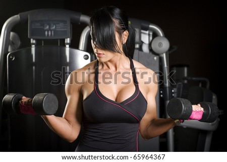 Muscular asian woman working out with weights - stock photo