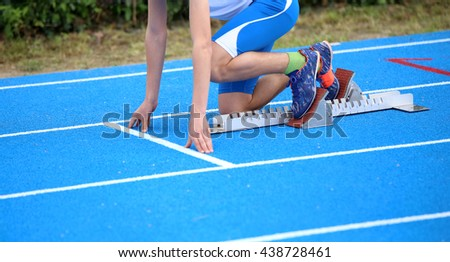 muscular athlete in the starting blocks of a athletic track before the start