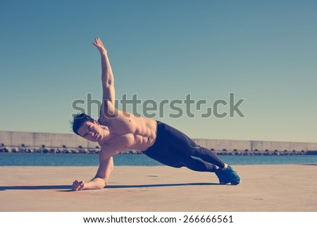 Muscular athlete with naked torso doing hand stand exercise for abdominal (intentional vintage color) - stock photo