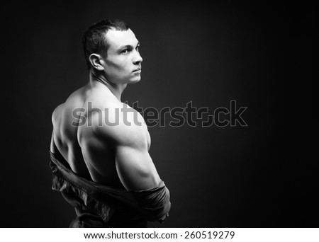 muscular athletic guy takes off his shirt on a dark background - stock photo