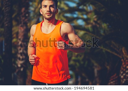 Muscular athletic man in the bright sportswear running on the jogging track and looking at the camera - stock photo