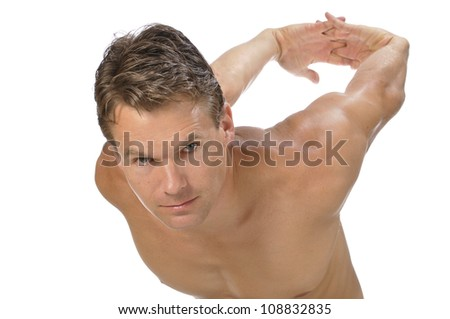 Muscular athletic shirtless man stretching biceps and shoulders with arms behind back on white background