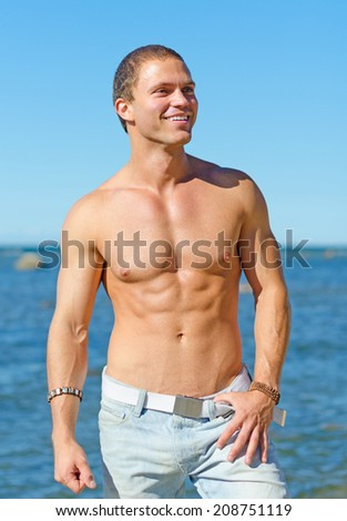 Muscular attractive man posing near the sea. - stock photo