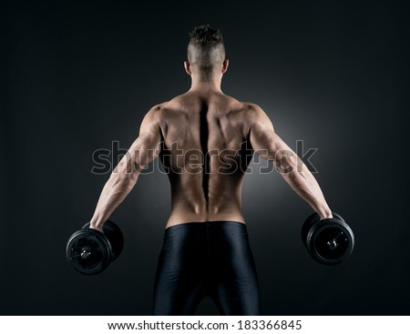 Muscular attractive man weightlifting on dark background. - stock photo