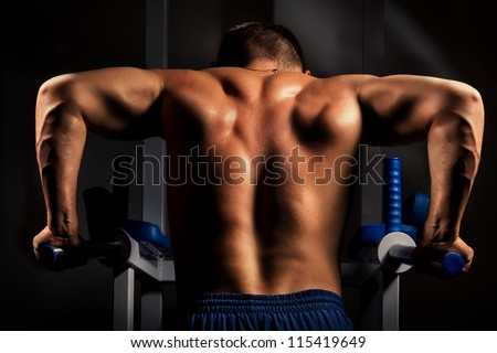 Muscular back of young bodybuilder training in dark background - stock photo