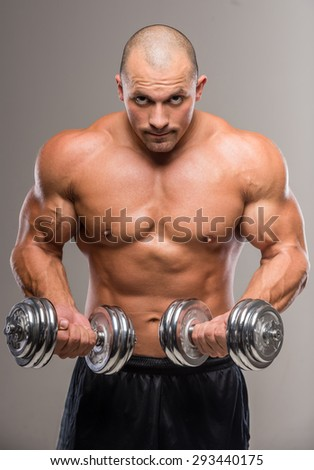Muscular bald man posing with weights on a gray background.