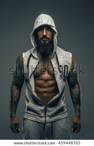 Muscular bearded man in white hoodie isolated on a grey background. - stock photo