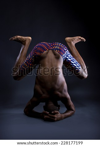 muscular black man doing upside down yoga on grey background - stock photo