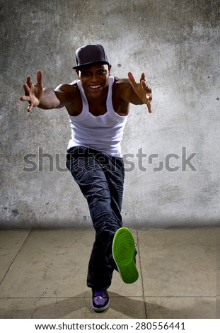 Muscular black man posing hip hop dance choreography on concrete background.  He is dancing in an urban setting. - stock photo