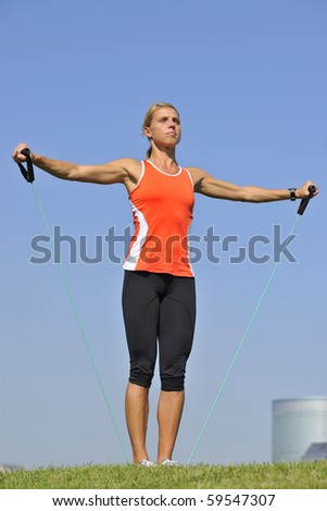 Muscular blond woman doing strength training in urban park with rubber exercise cord skyline in background.