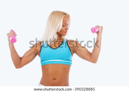 Muscular blond woman holds a pair of dumbbells. Isolated on a white background. - stock photo