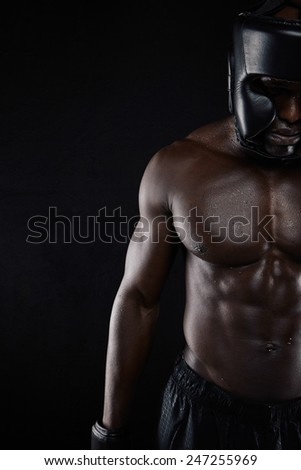 Muscular body of african male boxer against black background with copy space. Cropped image of male in boxing gear. - stock photo