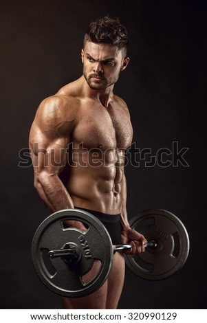 Muscular bodybuilder guy doing exercises with big dumbbell over black background - stock photo