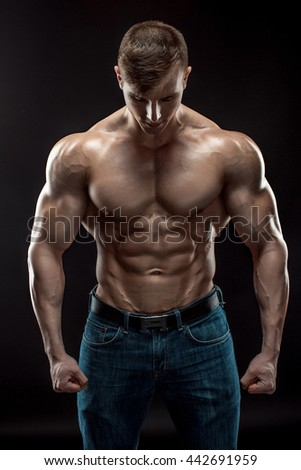Muscular bodybuilder guy doing posing over black background - stock photo