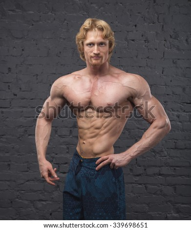 Muscular bodybuilder man. Man with large muscles of the body on a gray brick wall background. Handsome power athletic man. Copy space for text. Posters, advertising for gym. Healthy muscular young man