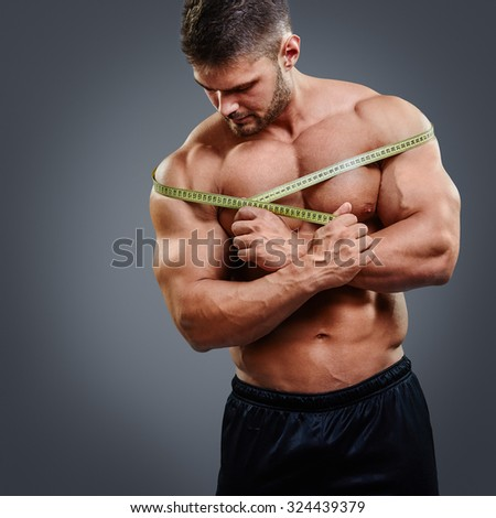 Muscular bodybuilder measuring shoulders with tape measure, standing isolated over gray background. Fitness male model shoulder gain concept. - stock photo