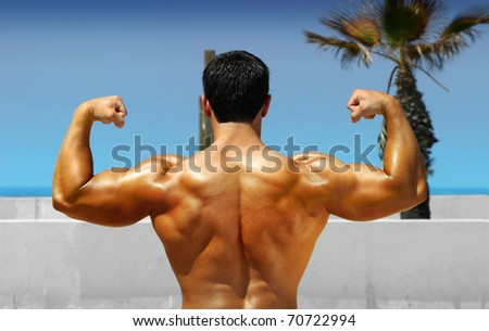 Muscular bodybuilder showing his back on the beach - stock photo
