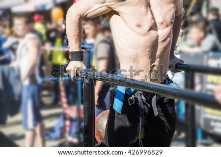 Muscular bodybuilder working out on street doing exercises on parallel bars. Athletic male naked torso. no face, unrecognizable person.