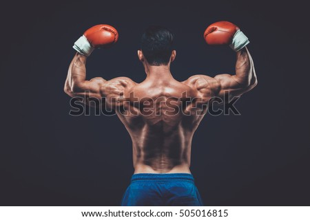 Muscular boxer in studio shooting, on black background.