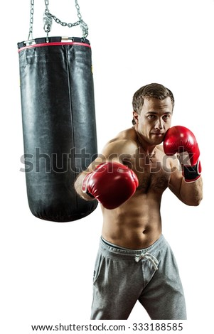 Muscular boxer near the boxing bag. Isolated on white background. - stock photo