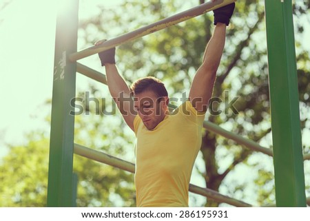 Muscular built young athlete working out in an outdoor gym - stock photo