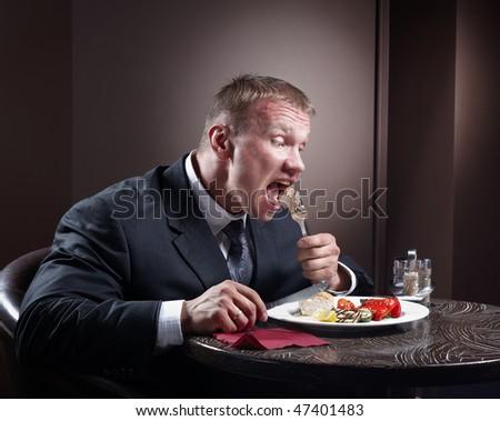 Muscular businessman eating - stock photo