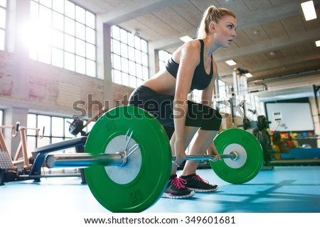 Muscular caucasian woman in a gym doing heavy weight exercises. Young woman doing weight lifting at health club. - stock photo