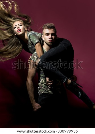 Muscular cool man holding on shoulders sexual cute young blonde woman with long curly streamed hair looking straight dressed in military style t-shirts posing on purple background studio, vertical - stock photo