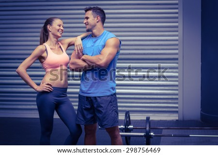 Muscular couple discussing together with arm on shoulder - stock photo