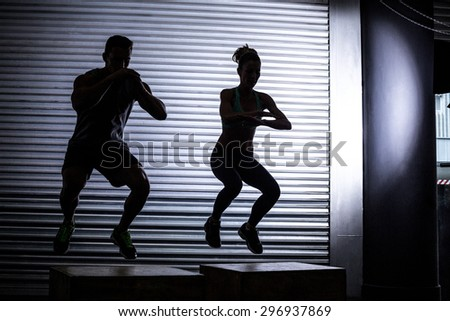 Muscular couple doing jumping squats on a wooden box - stock photo