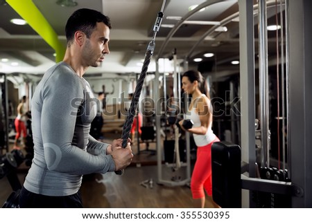 Muscular couple doing powerful exercise - stock photo