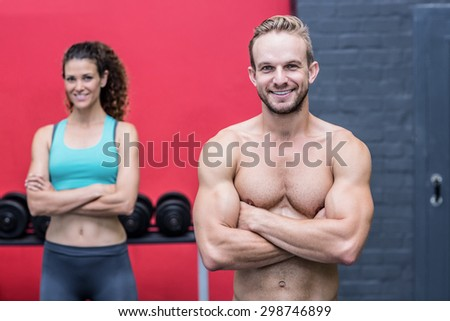 Muscular couple looking at the camera with man ahead - stock photo