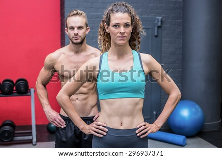 Muscular couple looking at the camera with woman ahead - stock photo