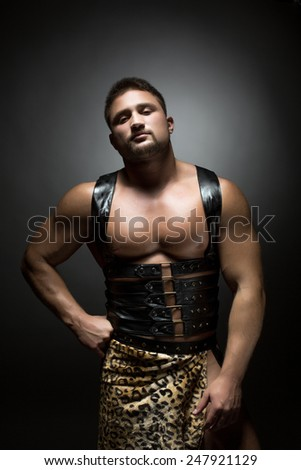Muscular dancer dressed as prehistoric man - stock photo