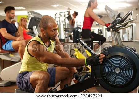 Muscular ethnic man training in gym.