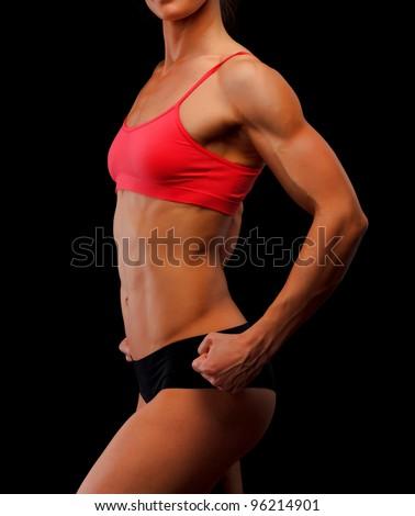 Muscular female body against black background - stock photo