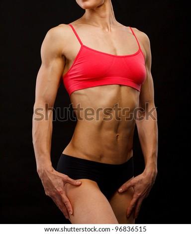 Muscular female body against black background. - stock photo