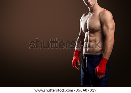 Muscular Fighter With Red Bandages Isolated On Brown Background - stock photo
