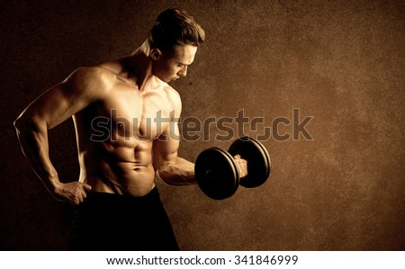Muscular fit bodybuilder athlete lifting weight on grungy background