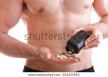 Muscular fit man isolated offering pills drag tablet in bottle, box with supplements - stock photo