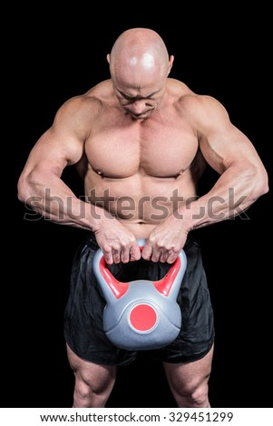 Muscular fit man lifting kettlebell against black background - stock photo