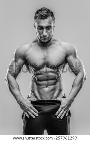 Muscular fit man standing over gray background. HDR monochrome